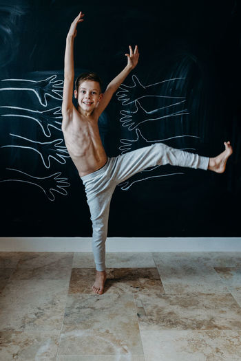 Portrait Of Shirtless Boy Dancing Against Wall