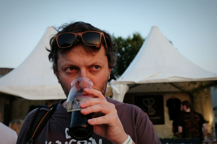 Close-Up Of Man Drinking Craft Beer Against Tent During Sunset