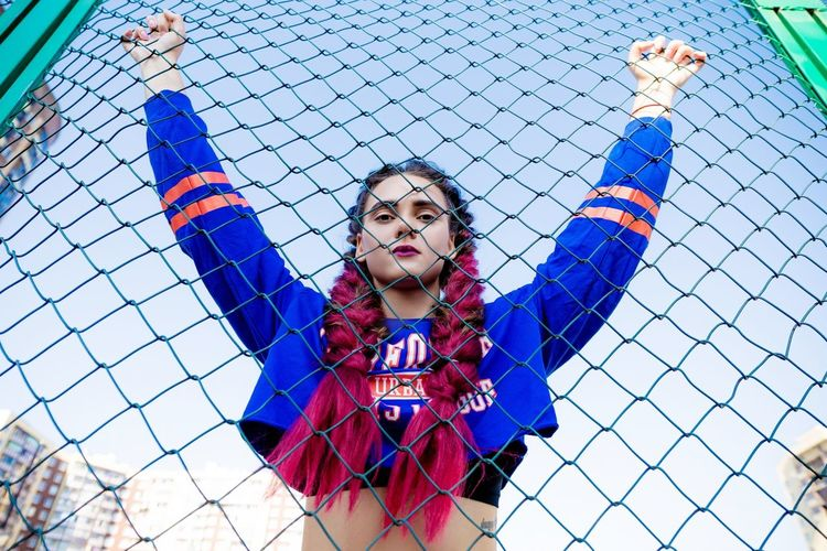 Portrait of young woman with arms raised standing by chainlink fence against sky