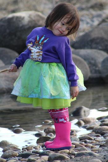 Cute girl standing on rock