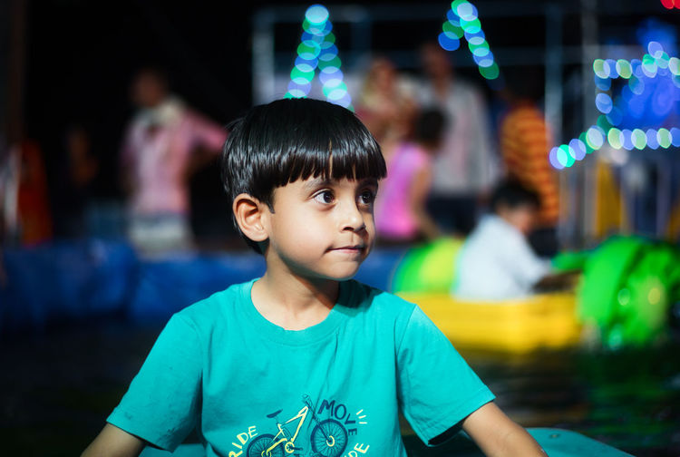 Cute Boy Looking Away Against Illuminated Lighting Equipment At Night