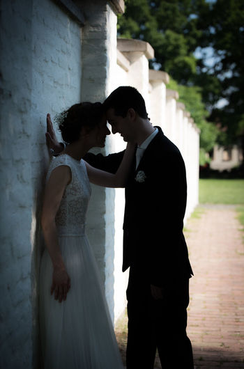 Side view of romantic bride and groom standing by wall on footpath