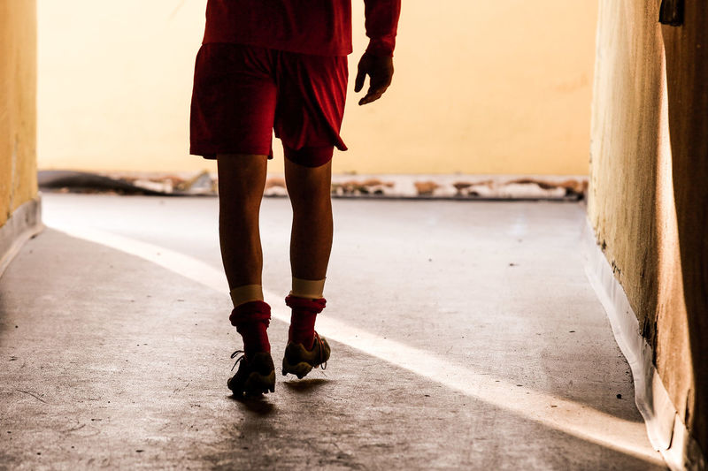 Low Section Of Sportsman Walking In Corridor
