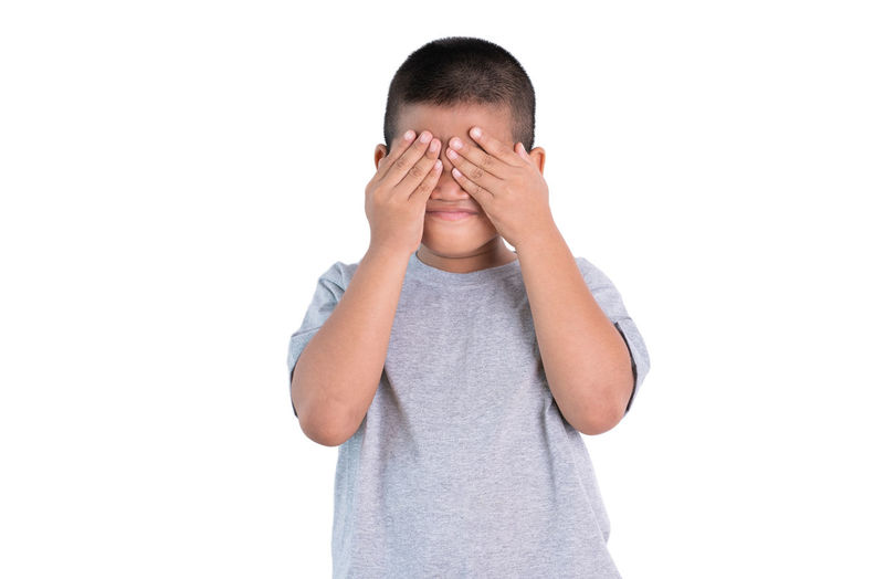 Midsection of boy covering face against white background
