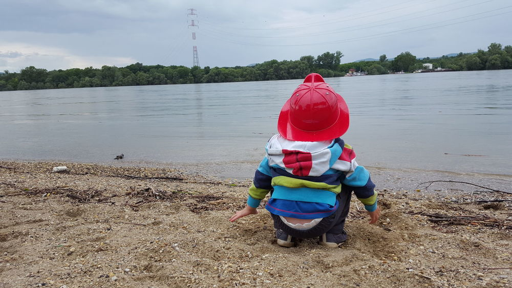 On the banks of the Danube River, my little friend, Oscar ❤ Danube Danube River Banks Of River Little Boy Calmness Children Photography Point Of View Watching The River EyeEm Best Shots Eyeem Hungary Duna Dunakeszi Hungary Red Hat Firefighter Little Firefighter Fireman Firefighter Hat