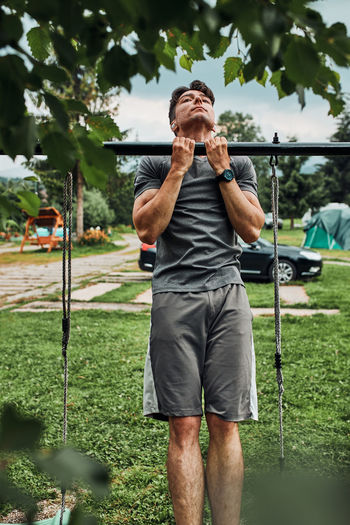 Young man doing pull-ups on pull-up horizontal bar during his calisthenics workout on a camping