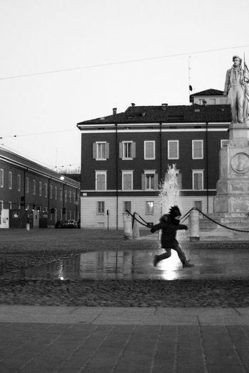 21/01/18 _ Modena Piazza Roma è piena di gente. Le luminarie di Natale illuminano ancora la piazza e dalla pista di pattinagio arrivano schiamazzi e risate. Mio padre e io stiamo passeggiando per il centro. Dice che sono troppo piccolo per pattinare. Cadrei e mi farei male dice. Però io mi annoio, uffa. Non mi piace camminare, mi fanno male i piedi e ho freddo. <<La fontana però non è da grandi!>> Scappo. Corro più veloce che posso verso la fontana. Mio padre non riesce a prendermi. Non ci penso neanche due volte e mi tuffo nella fontana. Mi sono bagnato tutto ma è divertente. Mio padre subito mi sgrida ma mi lascia fare altri due o tre salti sopra gli spruzzi della fontana. È questo che mi piace fare. Cogliere l' attimo e raccontare una storia che ho visto. Questo bimbo era super felice di saltare nella fontana e bagnarsi tutto. E io sono felice di aver immortalato il momento. Peccato non avere la possibilità di dare la foto al sarebbe piaciuto. /// Bnw Blackandwhite Child Streetphotography Streetart Modena Modenacentro Accademia Statue Street Streetphoto_bw Bnw_shot Italy Italia Urban Urban Geometry Architecture One Person Built Structure Real People Day Building Exterior Outdoors Transportation People One Man Only City EyeEmNewHere