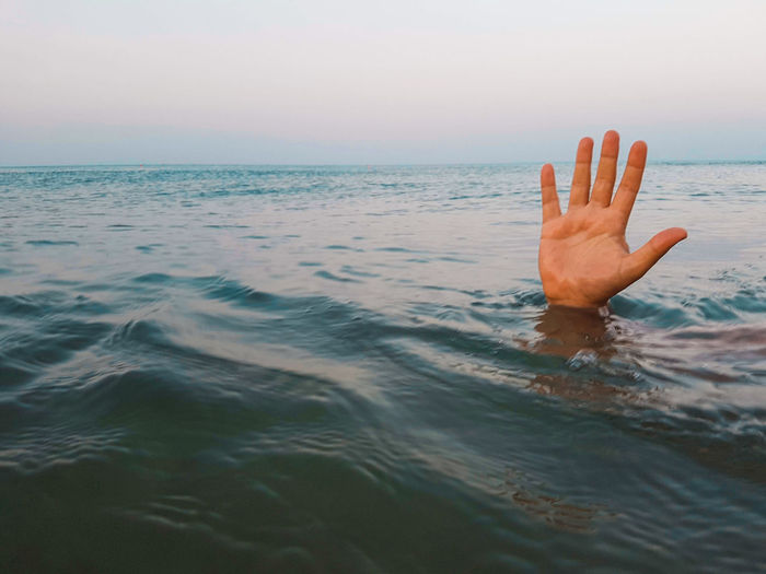 Close-up of hand in sea against sky