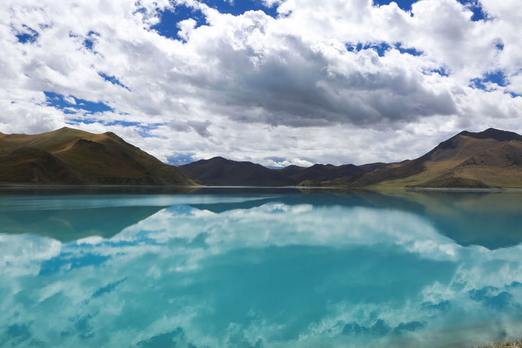 Lake by mountains with reflection of clouds and sky seen in water