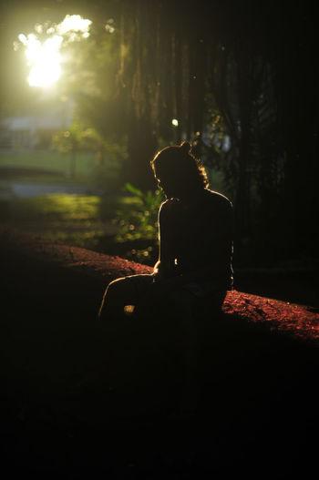 Man Sitting On Land At Sunset