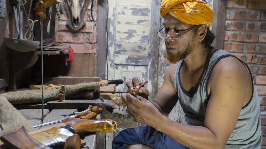 Local demonstrate on making art of crafting malay traditional asymmetrical dagger called keris