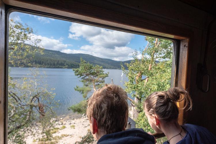 Siblings looking at lake through window