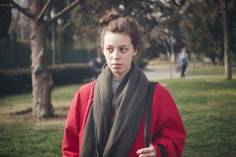 Woman looking away while standing at park