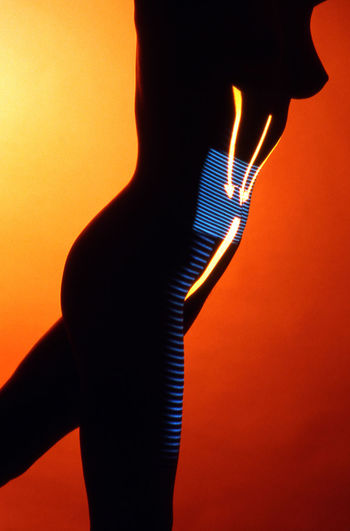 Close-up of silhouette woman against illuminated wall