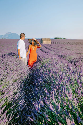 Couple holding hands standing at flowering field