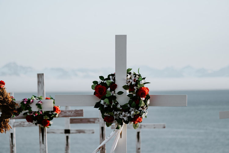 Close-up of flowers on cross by sea against sky