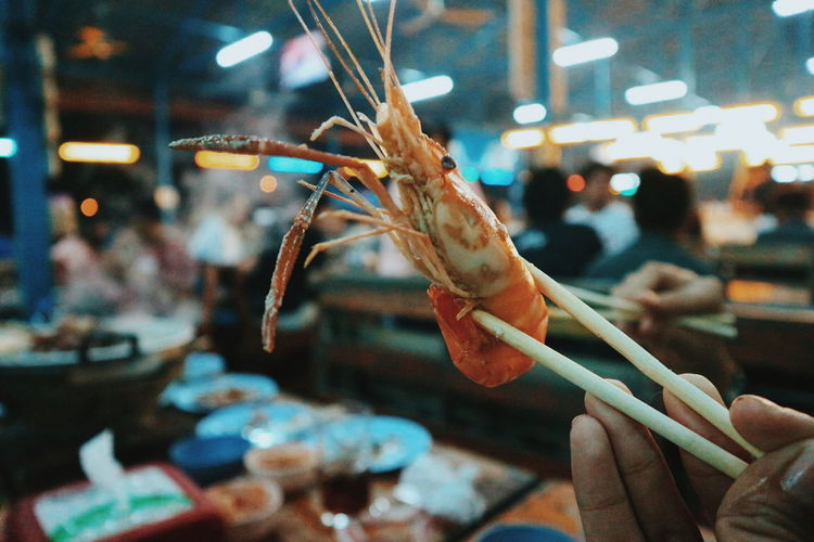 Cropped hand holding prawn in restaurant