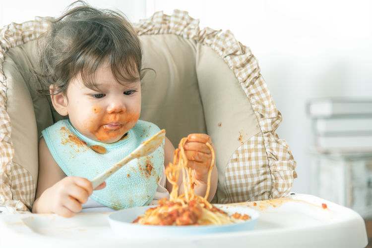 Cute girl eating food on table
