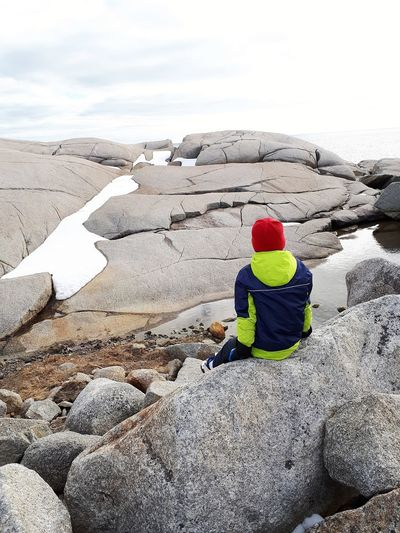 Rear view of man on rock against sky during winter