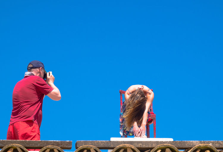 Man photographing woman sitting on chair against clear sky