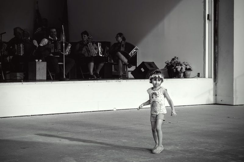 Young Girl Standing In Front Of Stage At A Concert