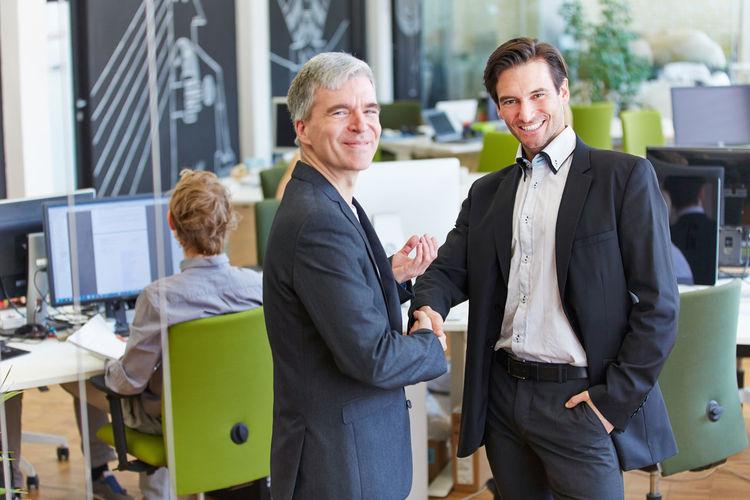 Portrait Of Smiling Businessmen Handshaking In Office