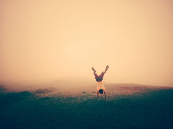 Rear view of man practicing handstand on grassy field during foggy weather