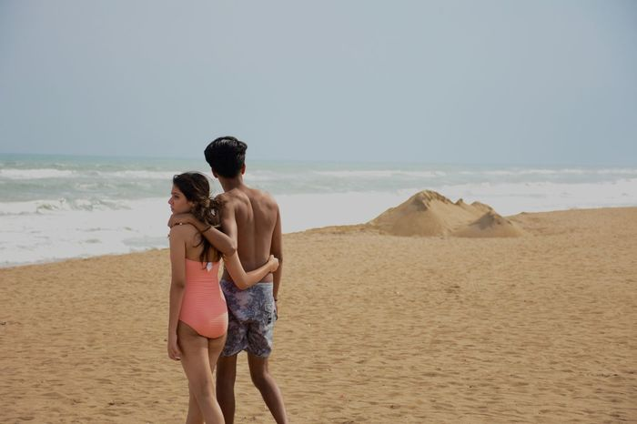 Beach Beauty In Nature Clear Sky Day Full Length Horizon Over Water Leisure Activity Lifestyles Love Men Nature Outdoors Real People Rear View Sand Scenics Sea Shirtless Sky Standing Togetherness Two People Vacations Water Young Women