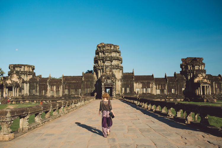 Rear View Of Woman Standing Against Historic Building Against Sky