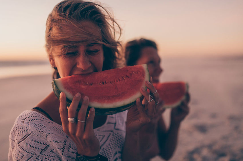Watermelon Eating Beach Holding One Person Sea Leisure Activity Nature Food Adult Sunset Sand Food And Drink Young Adult Portrait Headshot Sky Outdoors Freshness Fruit