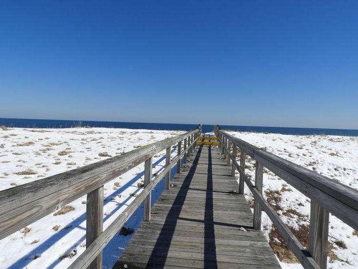 Boardwalk Photography Boardwalk To Ocean Boardwalk Wooden Boardwalk Boardwalk Through Sand Dunes Blue Sky Snow Boardwalk On Plum Island Massachusetts Ocean Photography Nature Calm Tranquility Tranquil Scene Outdoors Beauty In Nature Nature Photography Sand Dune Photography Ocean Clear Sky Sea Beach Sunlight Sand Cold Temperature Blue Wood - Material Full Length Winter Railing Bridge - Man Made Structure
