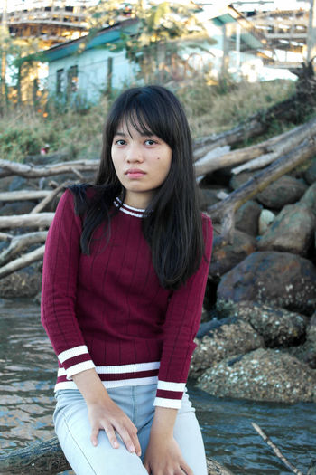 Portrait of girl sitting on wood in river