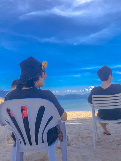 Rear view of people sitting on beach