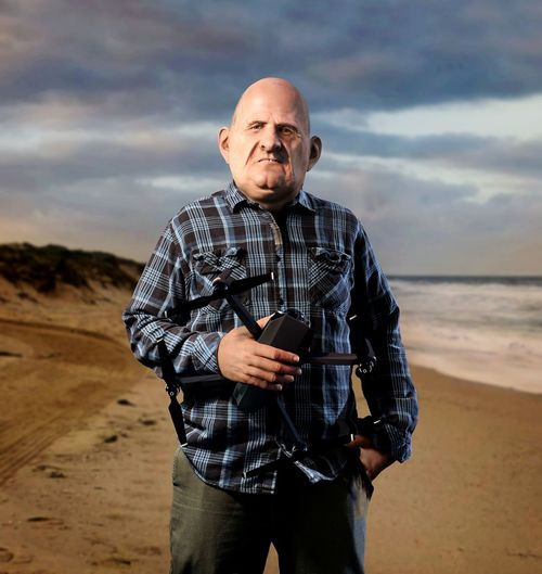Portrait of mature man with camera standing at beach against cloudy sky