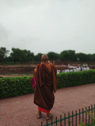Rear view of monk wearing traditional clothing standing on footpath
