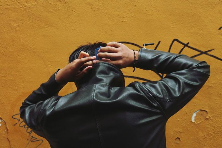 Rear view of man wearing leather jacket against wall