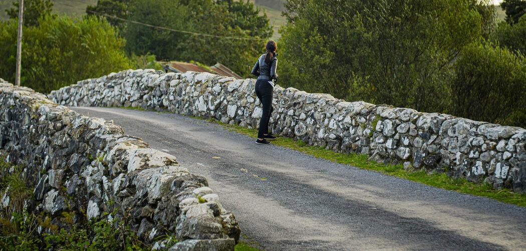 Rear view of man walking on rocks against trees