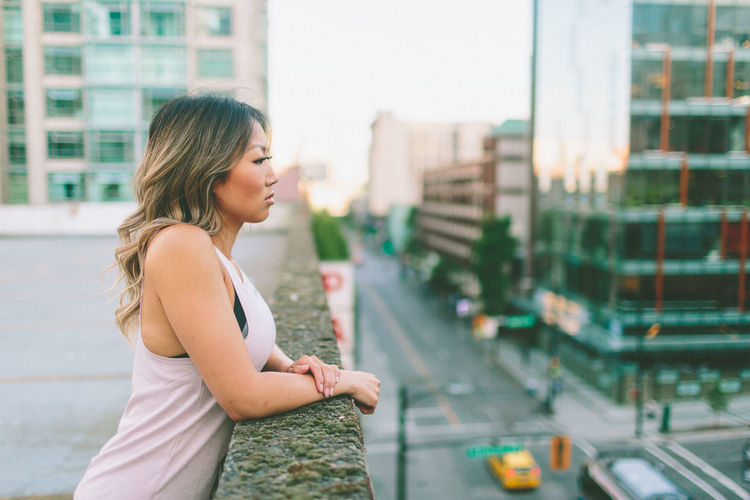 Side View Of Young Woman Standing On Building Terrace In City
