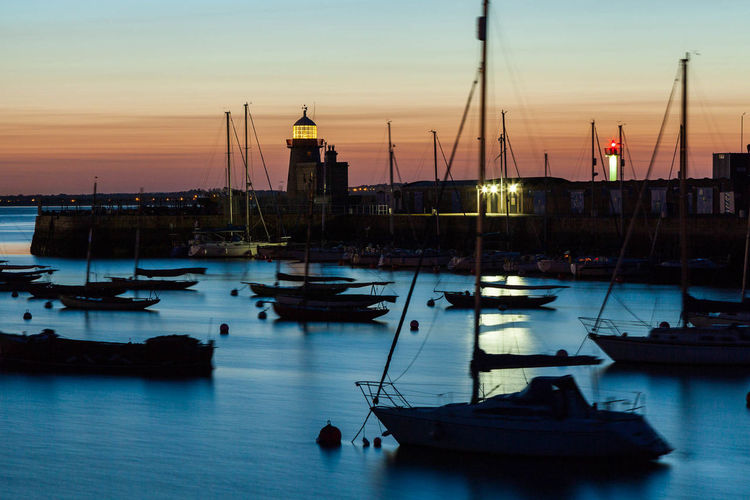 Sailboats moored on sea against sky at sunset