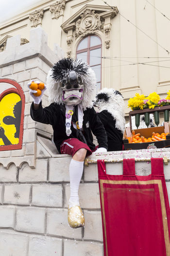 Steinenberg, Basel, Switzerland - March 8, 2017. Close-up of a Waggis on top of a carnival float throwing oranges into the watching crowd. Basel Basel, Switzerland Carnival Carnival Crowds And Details Disguise Fun Funny Waggis Arts Culture And Entertainment Building Exterior City Costume Full Length Leisure Activity Mask - Disguise Oranges Parade Parade Float People Portrait Real People Swiss Throwing  Traditional Festival Two People