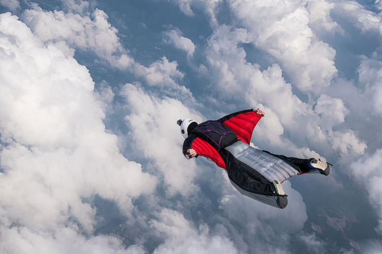 Person Flying Above Clouds In Wingsuit