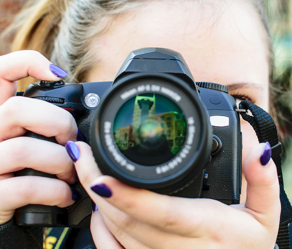 Close-up of teenage girl photographing with camera