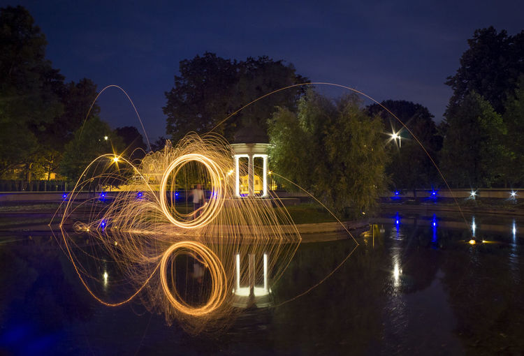 Person spinning wire wool on river at night