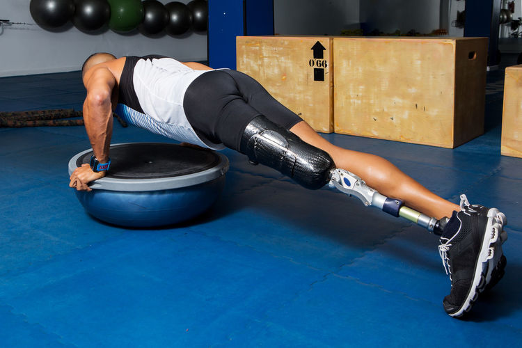 Determined Disabled Man Doing Push-Ups On Bosu Ball At Gym