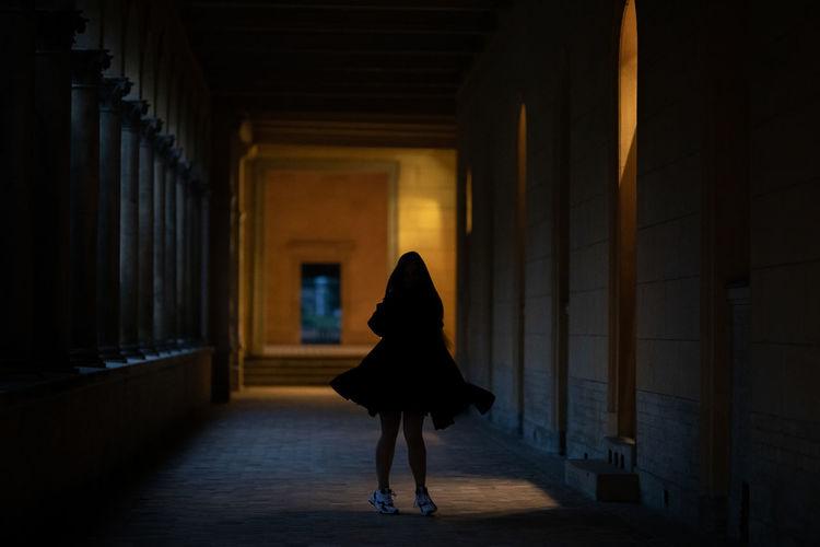 Woman walking in corridor of building