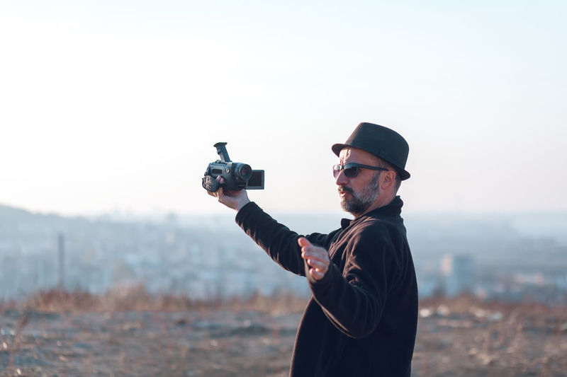 Man holding camera while standing on land against sky