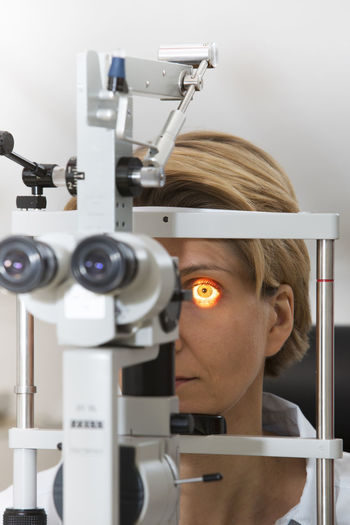 Mature woman looking through eye test equipment