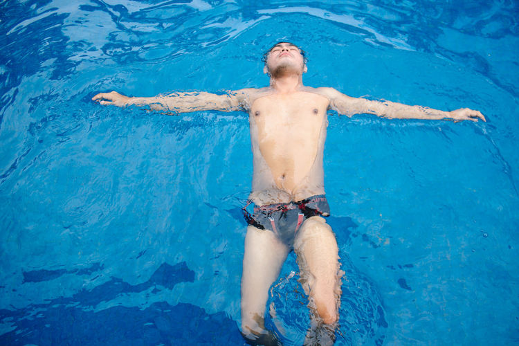 High angle view of shirtless man floating on water