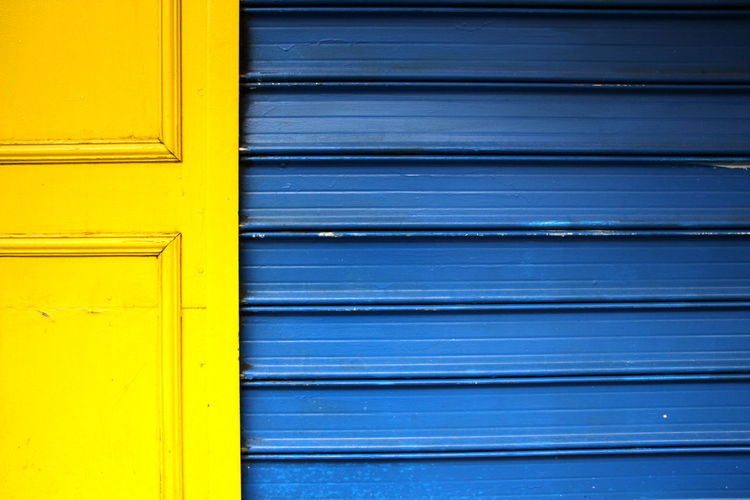 Close-up of yellow door against blue wall