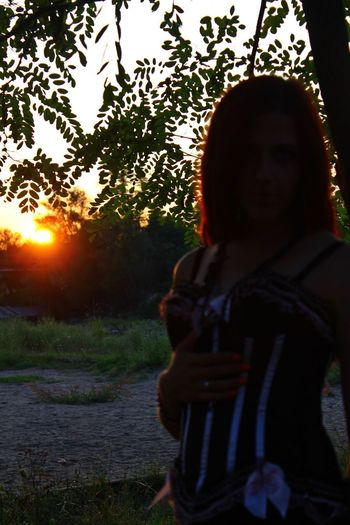 Portrait of young woman standing by tree against sky during sunset
